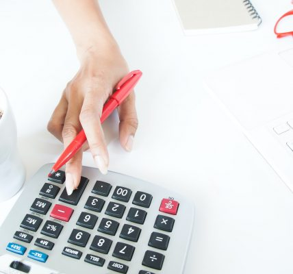 Business woman using calculator and laptop on white desk, Accounting and tax concept